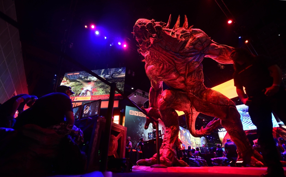 Gaming fans play 'Evolve' on Playstation at the annual E3 video game extravaganza in Los Angeles, California on June 10, 2014, where Microsoft and Sony are battling for the hearts of hard core gamers whose devotion could determine whether Xbox One or PlayStation 4 rule console play and Internet Age entertainment.. AFP PHOTO/Frederic J. BROWN