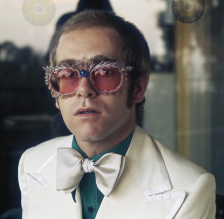 English pop singer Elton John in a white jacket and rococco spectacles, circa 1978. (Photo by Terry O'Neill/Hulton Archive/Getty Images)