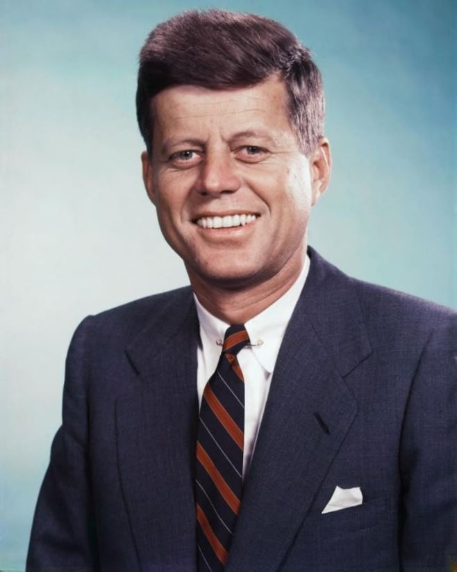 John-F-Kennedy-smiling-in-this-photo-in-a-navy-jacket-paired-with-a-stripe-tie-and-white-linen-pocket-square-720x900