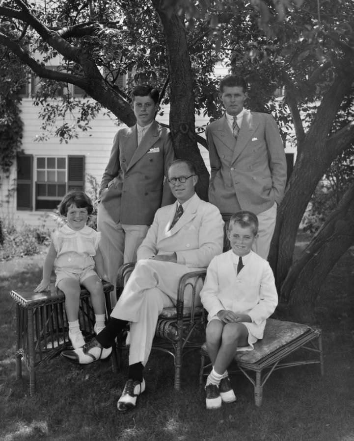 Young-JFK-with-double-breasted-combination-collar-pin-with-father-Joe-and-siblings-721x900